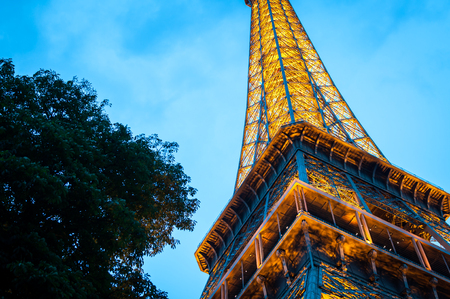 The Eiffel Tower seen from below in the evening on a blue night sky in Paris