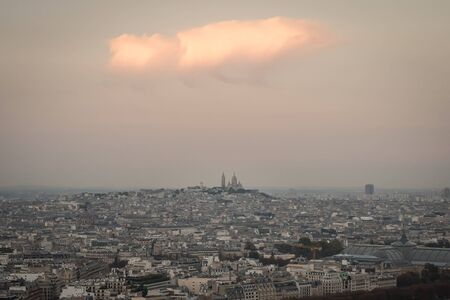 Cityscape of a white cloud over the Sacred Heart basilica and the roofs of Paris at evening