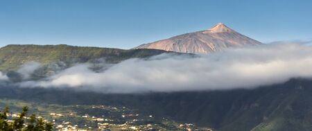 The city of Santa Cruz de Tenerife under the mist of El Teide volcano Imagens
