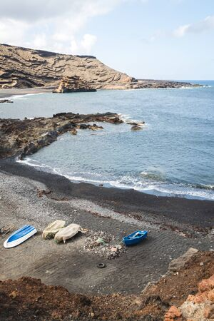 Boats on the black sand beach on the rocky point of El Golfo on the island of Lanzarote - Canary islands Imagens