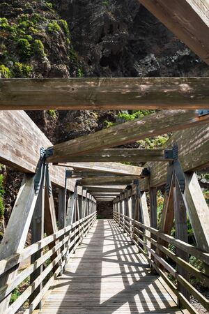 Wooden walkway leading to the foot of the mountain in Madeira