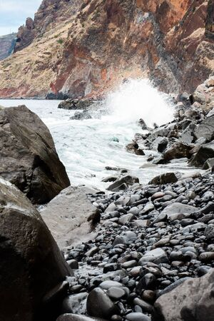 Ocean unchained on a pebble beach at the foot of a rocky cliff in Madeira
