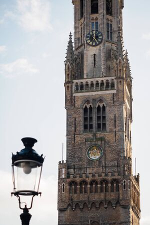 Close-up on the Belfry of Bruges with a lamp in the market square, Belgium