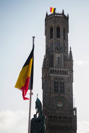 Belfry of Bruges with the Belgian flag from the market square, Belgium
