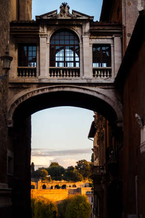 Passage to the ruins under an old footbridge between two typical building in Rome, Italy