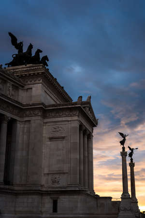 Angels on the columns of the Vittorio Emanuele II monument at sunset, Rome, Italy