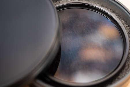 Polarizing filter for reflex camera lens in its elegant case reflecting the sky Archivio Fotografico