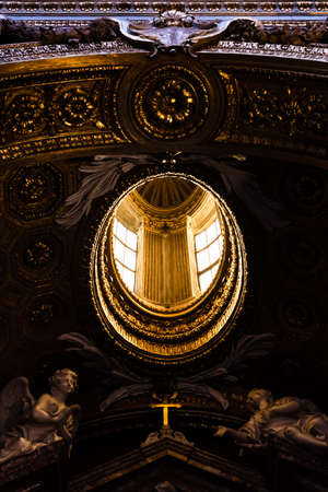 Skylight on statues of angels on the ceiling of a church in Rome, Italy