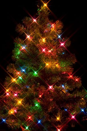 Christmas tree on black background with starburst lighting effect photo