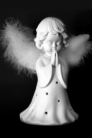 Praying Christmas angel in black and white on black background