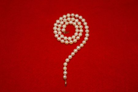 A beautiful question mark shaped pearl Necklace on a red felt background Imagens