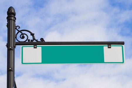 A green street sign on a decorative wrought iron post