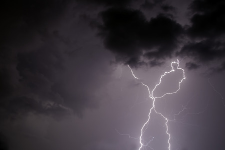 Twin strokes of lightning that splits in two half way through the stroke photo