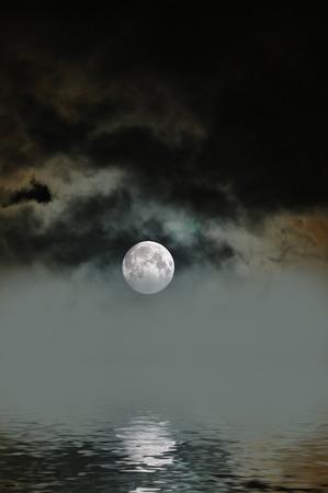 Rising moon on a foggy night over the ocean