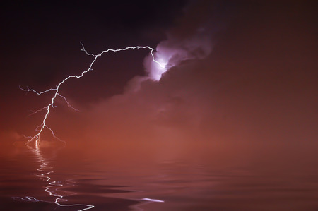Lightning over water on a foggy night Stock Photo