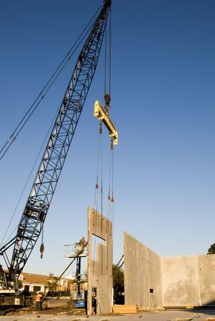 A crane setting a poured concrete two story wall in place Stock Photo