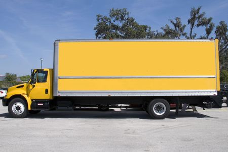 A yellow box delivery truck with blue sky Stock Photo