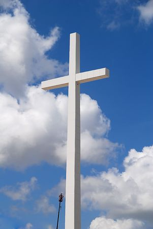 repaired: A huge religious cross being repaired on a beautiful partly cloudy day Stock Photo