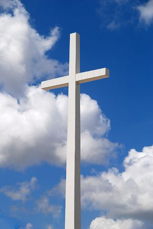 A huge religious cross on a beautiful partly cloudy blue sky
