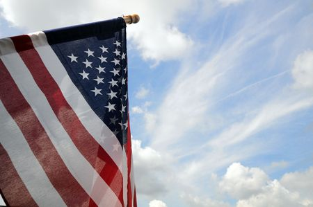 United States flag and pole with blue sky background and space for text