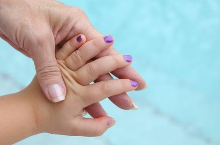 laquered: Grandmother holding her Granddaughters hand showing her nails at poolside