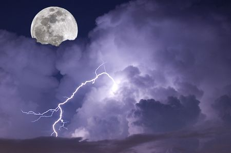 Telephoto image of a Lightning strike during a night storm with full moon rising