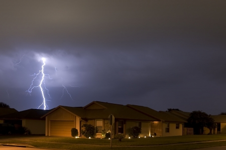 Lightning strike at night very near homes Stock Photo