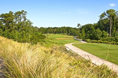 Golf Course showing tee fairway green and cart path with blue sky photo