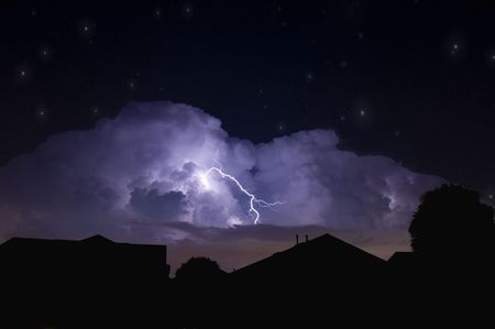 Lightning strike in a dark local neighborhood during a power outage and star field background Foto de archivo