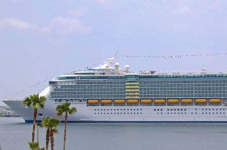 Large modern cruise ship setting sail with palm trees in foreground