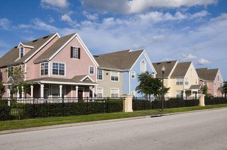 residential neighborhood: Colorido en la fila vallada casas con cielo azul