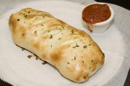 Golden brown italian strombli sub with marinara sauce Stock Photo