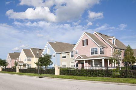 housing: Colorido en la fila vallada casas con cielo azul
