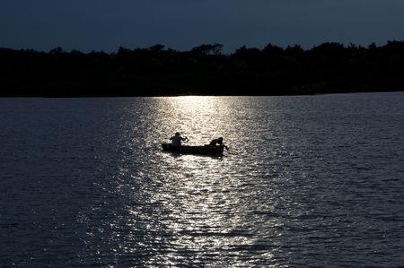 Lone Fisherman With Moon Light Reflecting on the Water photo