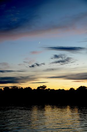 Colorful Sunset With Crescent Moon Visible With Water Reflection Stock Photo - 5411435