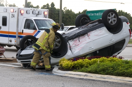 Rollover Vehicle Accident at Busy Intersection With Emergency Personnel to Assist photo