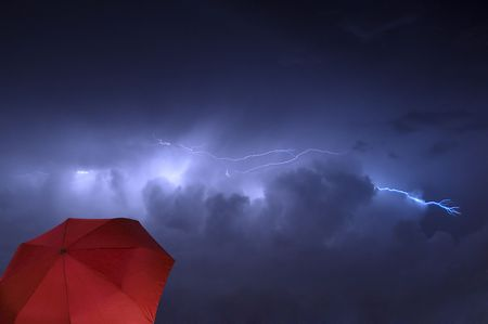 Cloud to Cloud Lightning Strike During a Rain Shower With a Red Umbrella in the Foreground photo