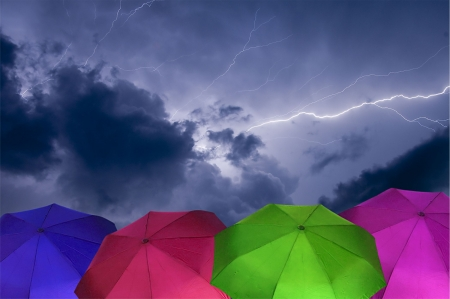 Cloud to Cloud Lightning Strike During a Thunder Storm With colorful Umbrellas in the Foreground Stock Photo