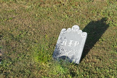 Scary Grave headstone with Rest In Peace engraved with long shadow near sunset photo
