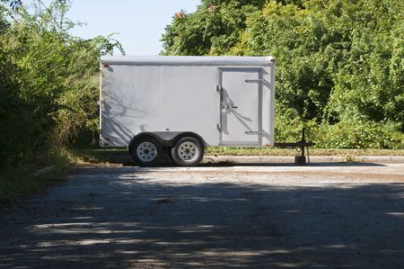 Parked Off White Utility Trailer waiting for pick up