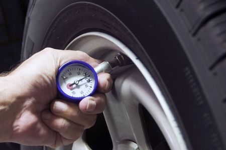 Checking tire pressure to improve gas mileage photo