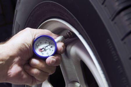 safety check: Comprobaci�n de la presi�n de los neum�ticos para mejorar el millaje de gas Foto de archivo