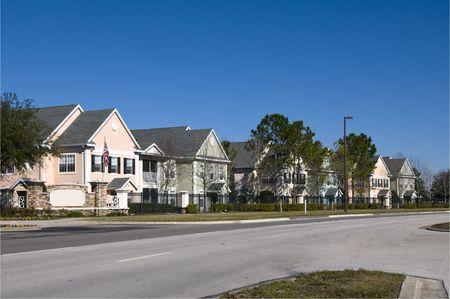residential neighborhood: Colorful cercados en casas de la fila con el cielo azul