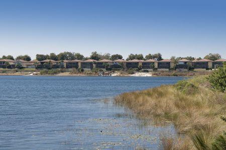 Condos and homes on a grass lake shore Stock Photo - 6568516