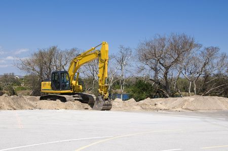 Bright yellow tract backhoe with blue sky photo