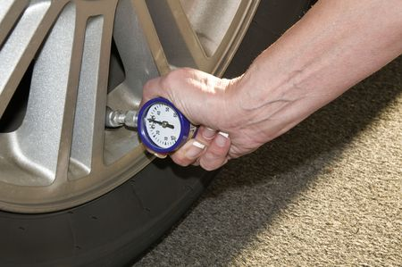 Woman checking her tire pressure to help increase her gas mileage photo