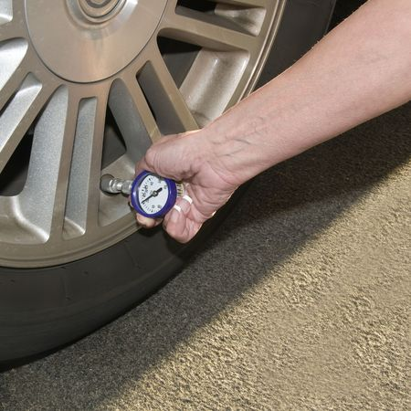 Woman checking her tire pressure to help increase her  gas mileage gauge indicates low pressure photo