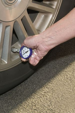 Woman checking her tire pressure to help increase her  gas mileage gauge indicates low pressure Stock Photo