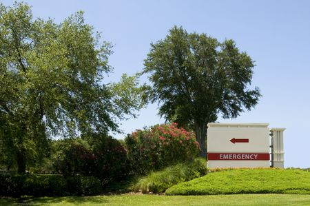 Emergency sign pointing to hospital entrance with blue sky background photo