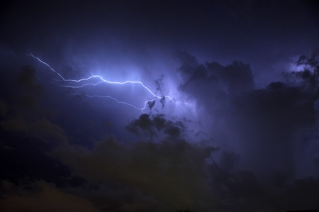 Blue Lightning strike surrounded by storm clouds and rain columns